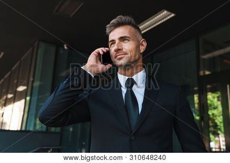 Photo of a optimistic mature grey-haired handsome business man outdoors at the street near business center talking by mobile phone.