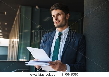 Image of a smiling young unshaved handsome business man outdoors at the street near business center holding documents.