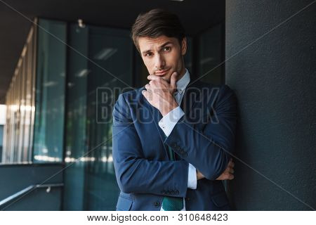 Photo of a thinking young unshaved handsome business man outdoors at the street near business center posing raise one eyebrow.