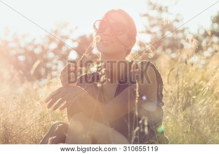 Woman in sunset. Lifestyle concept. Hipster woman relaxing in sunset in meadow. Healthy lifestyle. People lifestyle. Hipster people lifestyle. Relaxing. People. LIfestyle.