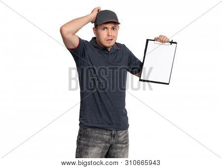 Portrait of unhappy Delivery man in cap holding clipboard with papers document. Confused handsome man looking on camera. Sad or Puzzled courier isolated on white background.