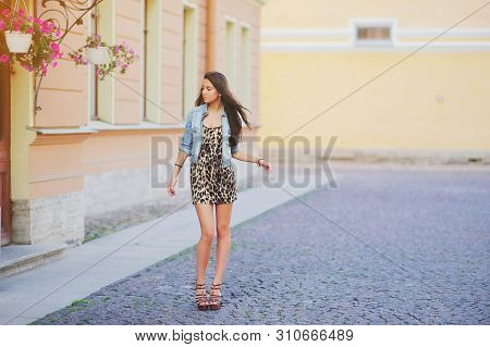 Stylish Long Hair Brunette Woman In A Leopard Animal Print Dress With Sexy Legs In Brown High Heel S