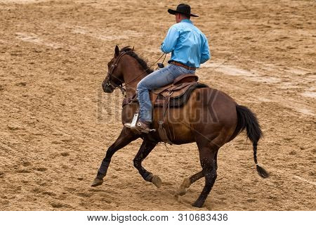 Rancher In Blue Jeans On Horse At Rodeo