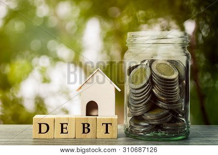Planning To Collect Money To Pay Outstanding Debts Concept. A Coins In Glass Jar With Wooden Block O