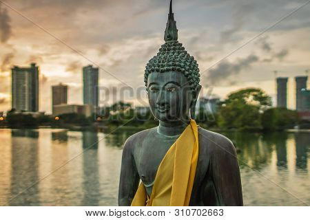 Statue Of Buddha Made Of Bronze In A Peacefull Pose, In Front Of A Cityscape On The Beira Lake In Co