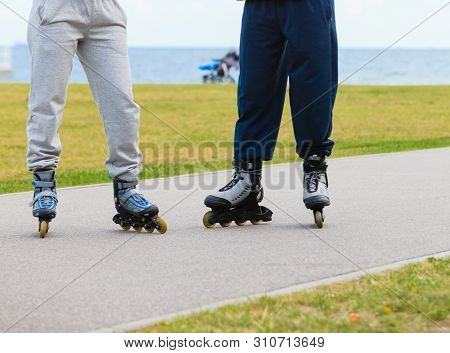 Active People Friends Rollerskating Outdoor. Woman And Man Riding Enjoying Sport, Shot Legs Only.