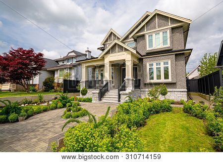 A Perfect Neighborhood. Nicely Landscaped Front Yard Of Luxury Residential House With Paved Pathway