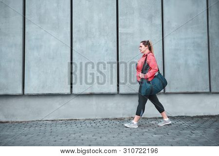 Workout Is Over. Back View Of Plus Size Woman In Sport Clothes Carrying Her Bag And Going Home After