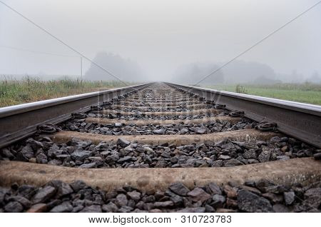 Train Rails. Looking Down The Tracks. Ground View Looking Down The Train Tracks Into A Dense Fog