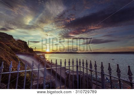 Sunset Lighting Up The Clouds At Dusk Over Mumbles Village And Swansea Bay, South Wales, Uk