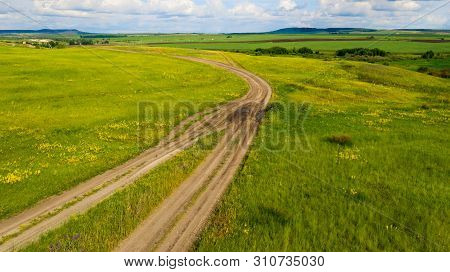 Aerial View From The Drone Of Summer Landscape With Rural Road Among The Hills.