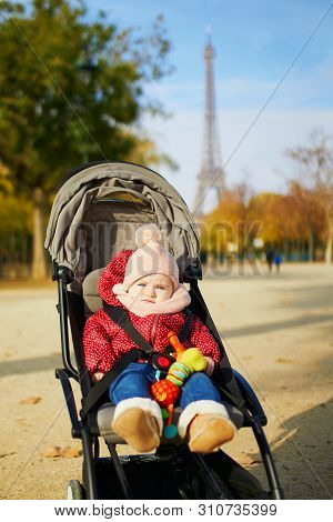 Adorable Little Girl In Bright Stylish Clothes Sitting In Pushchair Outdoors On A Fall Day In Paris,