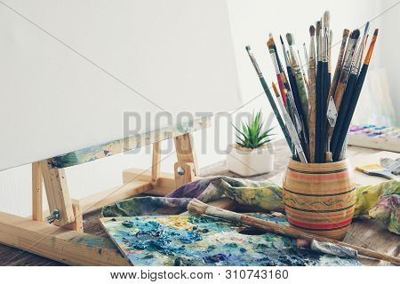 Artistic Equipment In Studio: Canvas On Wooden Easel, Paint Brushes, Paints And Used Palette.  Copy