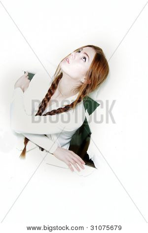 young woman looking out up from hole in paper