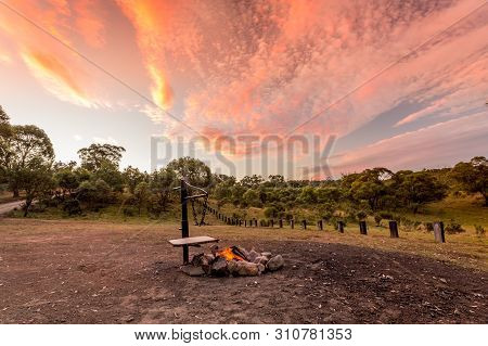 Campfire With Fire Burning In A Campground In The Australian Outback And A Beautiful Sunset Sky Over
