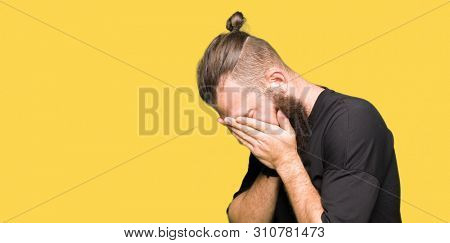Young blond man wearing casual t-shirt with sad expression covering face with hands while crying. Depression concept.