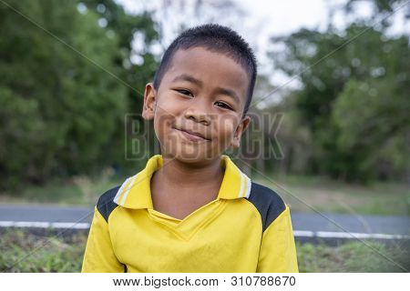 Asian Poor Child Laughing And Smile With White Teeth In Nature Background.close Up Headshot Asian Ki