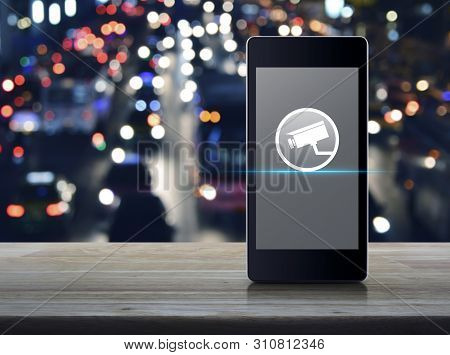 Cctv Camera Flat Icon On Modern Smart Mobile Phone Screen On Wooden Table Over Blur Colorful Night L