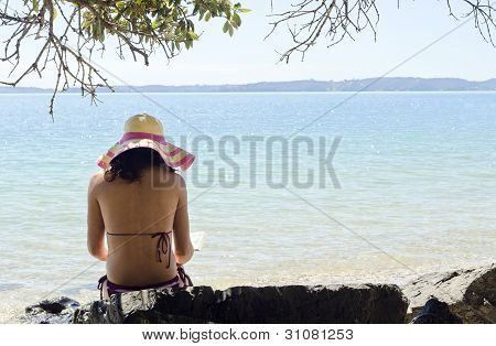 woman sitting on beach wearing hat and reading