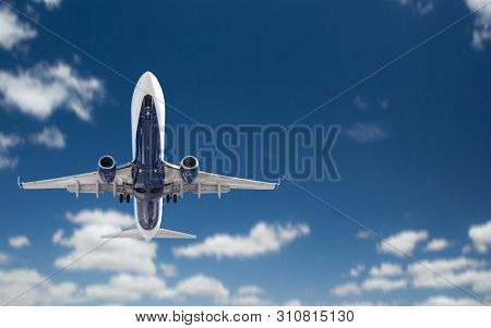 Bottom View of Passenger Airplane Flying In The Blue Sky.
