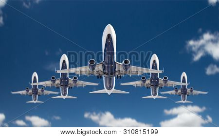 Bottom View of Five Passenger Airplanes Flying In Formation In The Blue Sky.
