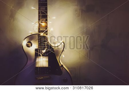 Merry Christmas Music Guitar Wrapped By Colorful Garland As A Gift Background. White Classical Guita
