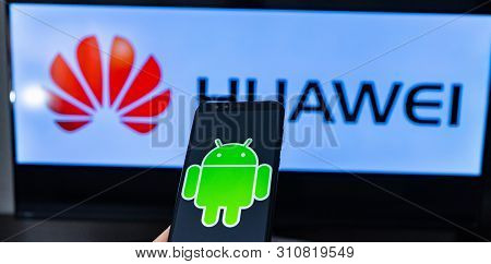 Magdeburg Germany - June 2019: A Man Holding Smartphone Honor. On The Screen, The Android Logo In Fr