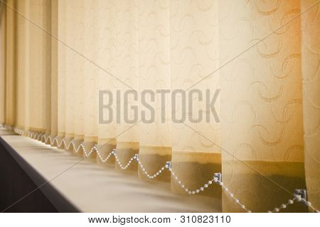 Yellow Vertical Blinds With A Chain In Office