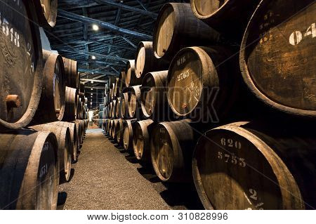 Porto, Portugal: Underground Of The Traditional Winery With Dark Wine Cellar Gallery And Numbers Of