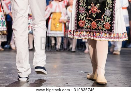 Close up of hands of young Romanian dancers perform a folk dance in traditional folkloric costume. Folklore of Romania poster