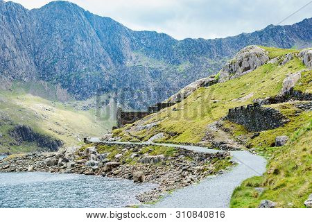Views Of Beautiful Lake In Snowdonia National Park, North Wales, Mountains On The Back, Stone Wall,