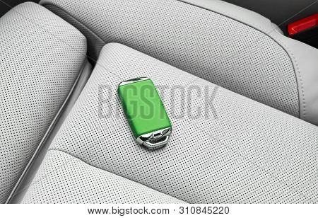 Closeup Inside Vehicle Of Wireless Green Leather Key Ignition On White Leather Seat. Wireless Start