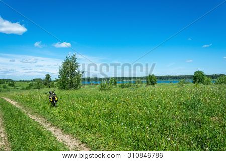 Tourist Bike On The Side Of A Field Road And A Big River Away On A Sunny Summer Day.