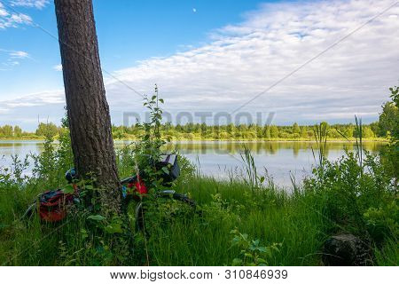 Tourist Bike On The Overgrown Shore Of A Small Lake On A Sunny Summer Day, Russia.