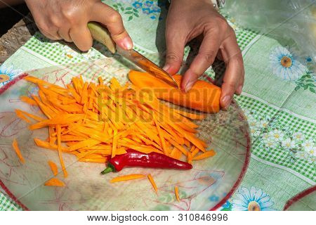 Cutting Carrots Into Thin Strips And A Pod Of Bitter Red Pepper On A Transparent Cutting Board.