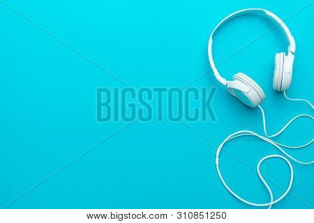 White Headphones With Cable. Top View Of Headphones On Turquoise Blue Background. Minimalist Photo O