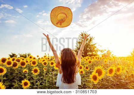 Happy Young Woman Walking In Blooming Sunflower Field Throwing Hat Up And Having Fun. Summer Vacatio