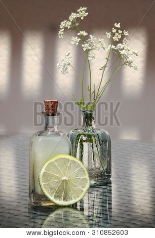 Still Life With Slice Of Lemon, Fresh Lemon Juice And Wild Flowers In A Small Vintage Glass Botlle.