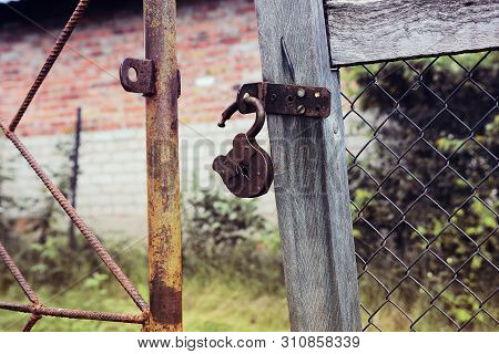 Rusty Padlock On An Old Village Gate. Intrusion Concept