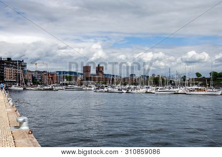 Oslo Cityhall And Aker Bridge. View From The Waterfront. Cityscape With Modern Architecture And Quay