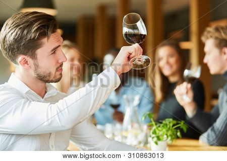 Young man with wine glass at a wine tasting proves quality of red wine