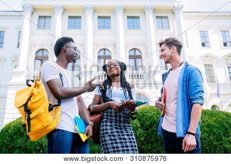 Three Positive Students From Different Coutries With Books And Backpacks Talking While Walking Again