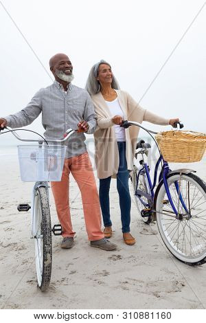 Front view of happy senior African-American couple standing with bicycles on the beach on cloudy day. Authentic Senior Retired Life Concept