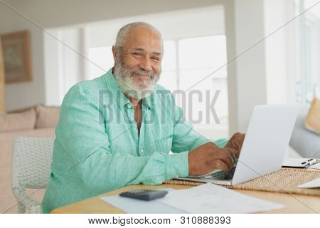 Side view of African-American smiling man using laptop on table indoor. Authentic Senior Retired Life Concept