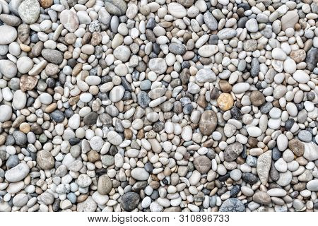 Beach stone pebbles. The texture of small stones. Can be used as a texture, background or wallpaper
