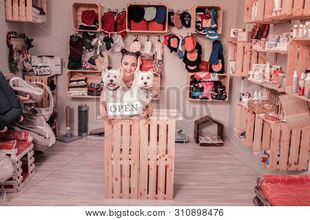 Dark-haired Woman Smiling While Opening Shop For Pets