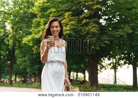 Portrait of beautiful woman in summer dress smiling and holding cellphone while walking through green boulevard poster
