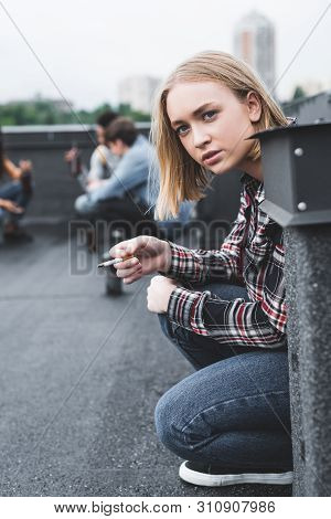 Selective Focus Of Blonde And Pretty Teenager Smoking Cigarette And Looking Away