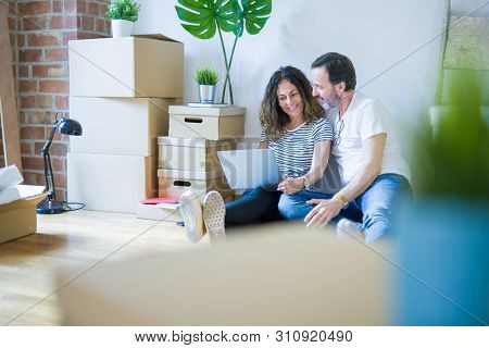 poster of Middle age senior romantic couple in love sitting on the apartment floor with boxes around and using computer laptop smiling happy for moving to a new home