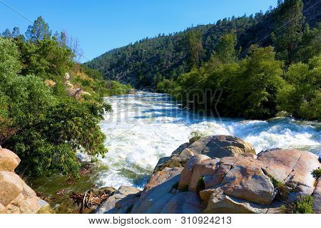 Roaring river with raging rapids surrounded by alpine forests taken at the Kern River in the Sierra Nevada Mountains, CA poster